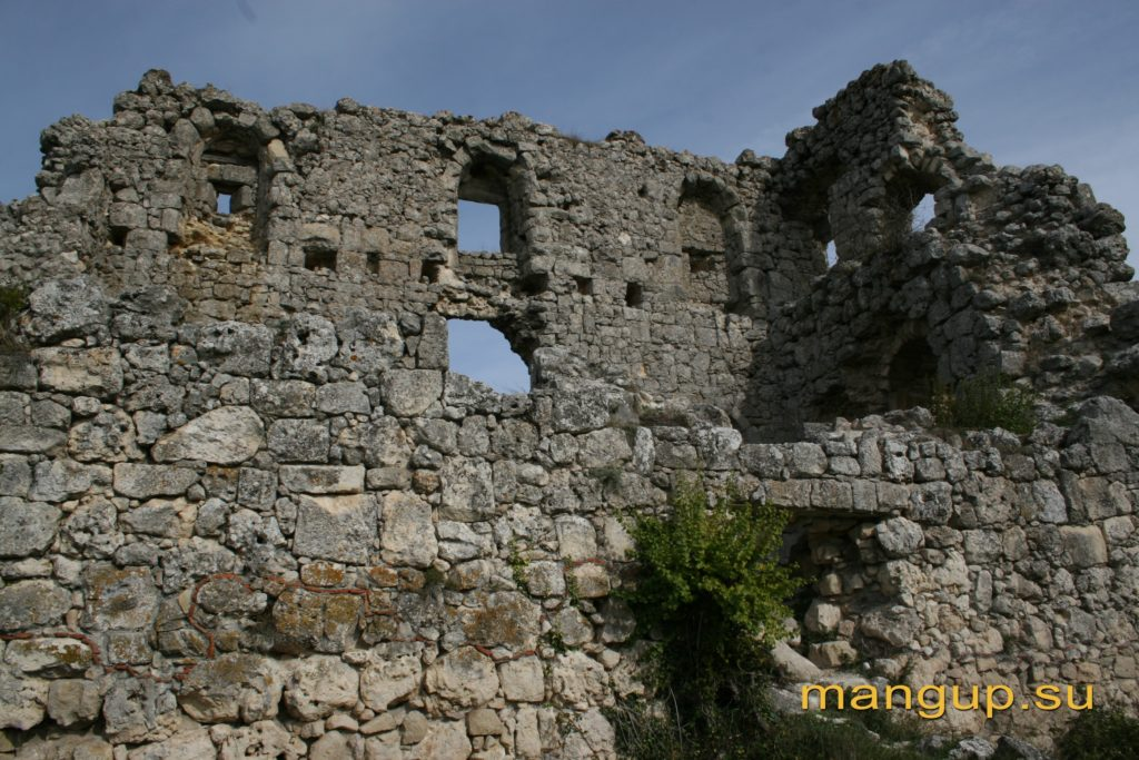 Северо-восточная стена донжона мангупской цитадели с окнами на уровне третьего этажа, два из которых превращены в амбразуры.